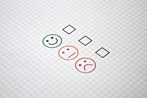 Es sind drei Smileys abgebildet, ein lachender, ein neutral schauender und ein traurig schauender, dahinter jeweils eine Ankreuzmöglichkeit.